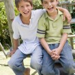 Two young male friends at a playground smiling — Stock Photo