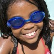 Young girl in swimming pool wearing goggles smiling — Stock Photo #4779944