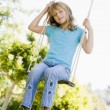 Young girl sitting on swing smiling — Stock Photo