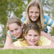 Three young girl friends piled on each other outdoors smiling — Stockfoto