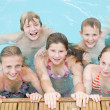 Five young friends in swimming pool smiling — Stock Photo