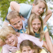 Five young friends piled on each other outdoors smiling — Stock Photo