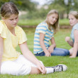 Stock Photo: Two young girls bullying other young girl outdoors