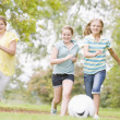 Three young girl friends playing soccer — Stock Photo