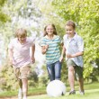 Three young friends playing soccer — Stock Photo