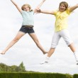 Two young girls jumping on trampoline smiling — Stock Photo