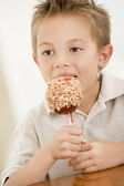 Young boy indoors eating candy apple — Stock Photo