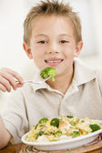Young boy indoors eating pasta with brocolli smiling — Stock Photo