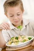 Young boy indoors eating pasta with brocoli — Stock Photo
