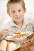 Young boy indoors eating soup — Stock Photo