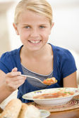 Young girl indoors eating soup smiling — Stock Photo