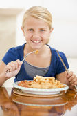Young girl indoors eating fish and chips smiling — Stock Photo