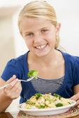 Young girl indoors eating pasta with brocolli smiling — Stock Photo