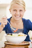Young girl indoors eating seafood smiling — Stock Photo