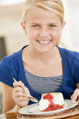 Young girl indoors eating cheesecake smiling — Stock Photo