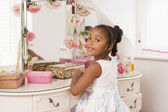 Young girl sitting at mirror in bedroom smiling — Stock Photo