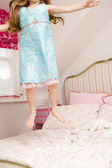 Young girl jumping on bed — Stock Photo