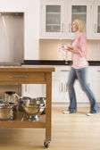 Woman walking in kitchen holding coffee — Stock Photo