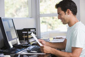 Man in home office using computer holding paperwork and smiling — Stok fotoğraf