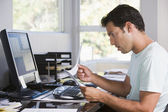 Man in home office using computer holding paperwork and looking — Stock Photo