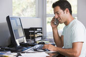 Man in home office on telephone using computer and smiling — Stockfoto