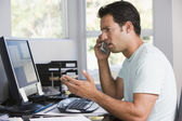 Man in home office on telephone using computer and frowning — Stock Photo