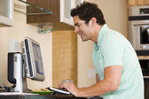 Man in kitchen using computer and smiling — Stockfoto