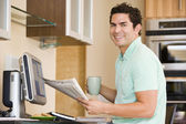 Man in kitchen with computer holding newspaper and coffee smilin — Stock Photo