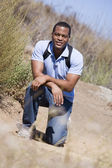 Gülümseyen plaj yolu üzerinde crouching adam — Stok fotoğraf