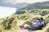 Man relaxing on cliffside path using binoculars — Stock Photo