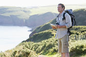 Man standing on cliffside path holding map — Stock Photo