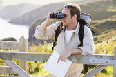 Man relaxing on cliffside path holding map and binoculars — Stock Photo