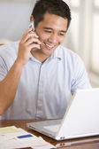 Man in dining room on cellular phone using laptop smiling — Stock Photo