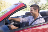Man driving convertible car smiling — Stock Photo