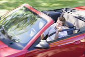 Man driving convertible car using cellular phone and smiling — Stock Photo