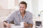 Man in kitchen reading newspaper and smiling — Stock Photo