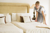 Maid making bed in hotel room — Stock Photo