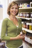 Woman in market looking at preserves smiling — Stock Photo