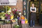 Vrouw werken bij bloem winkel glimlachen — Stockfoto