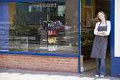 Woman standing in doorway of restaurant smiling — Stock Photo
