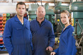 Three machinists in workspace by machine talking — Stockfoto