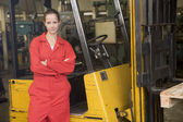 Warehouse worker standing by forklift — Stockfoto