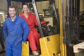 Two warehouse workers with forklift — Stok fotoğraf