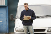 Deliveryperson standing with van writing in clipboard smiling — Stock Photo