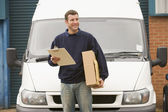 Deliveryperson standing with van holding clipboard and box smili — Stock Photo