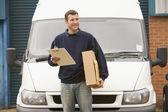 Pano ve kutu smili holding van ile deliveryperson ayakta — Stok fotoğraf