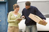 Two deliverypeople standing with van holding clipboard and box — Foto de Stock