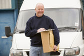 Deliveryperson standing with van with clipboard and box smiling — Stock Photo
