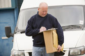 Deliveryperson standing with van writing in clipboard holding bo — Stock Photo