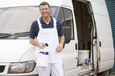 Painter standing with van smiling — Stock Photo